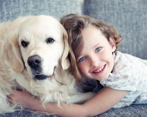 Young girl lying on sofa with pet dog