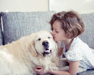 Young girl kissing pet dog