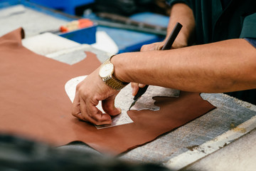 Person in workshop using template, cutting leather