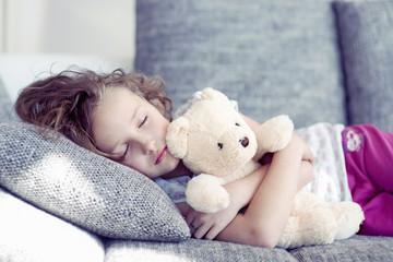 Young girl sleeping with teddy bear on sofa