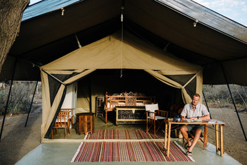 Man sitting at table in front of safari tent