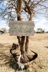 Warning sign on tree at safari camp, tanzania