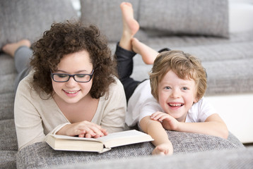 Teenage girl and brother reading book on sofa