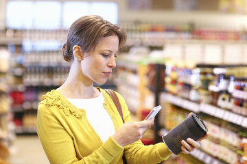 Woman scanning barcode in organic grocery store,