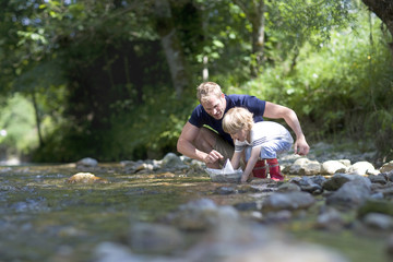 Father and young boy at river's edge floating paper boat