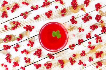 freshly squeezed red juice with green leaf currant and bunches of redcurrants on a white wooden table with old paintt. closeup flat lay