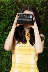 Asian woman happily using a retro camera