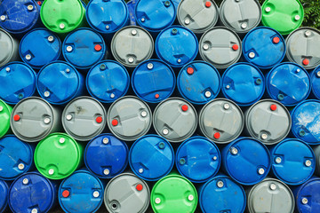 blue, grey and green oil barrels on a pile