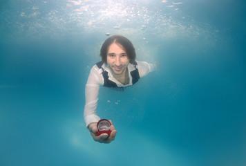 Groom presenting ring, underwater wedding in pool