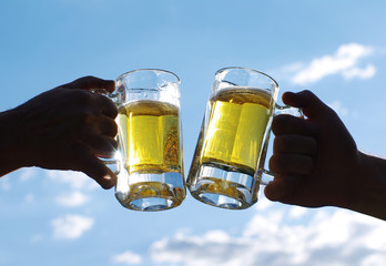 Cheers my friend! Two glasses of light beer hold male hands against the blue sky. Friends toasting with wheat beer