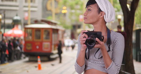 Woman with camera taking photo on San Francisco city street with