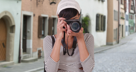 Woman with camera taking photo on Venice Italy city street