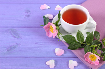 Cup of tea and wild rose flower on purple boards, copy space for text