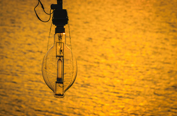 Lamp for fishing boat on sunset with blurred sea background.