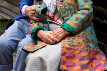Elderly couple sitting on a bench. Hands close-up.