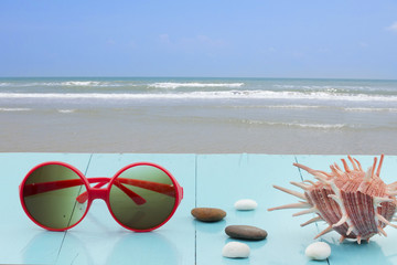 sunglasses place on wood table with sea and beach
