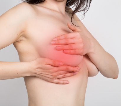 Breast cancer self check. Young woman examining her breast for lumps or signs of breast cancer. healthy lifestyle concept