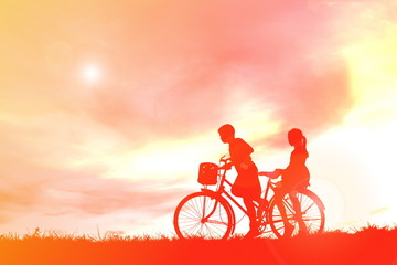 Silhouette children and bicycle at sunset