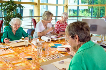 Group of cheerful older students painting together.