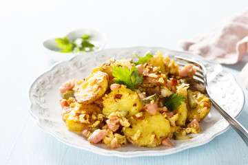 Fried potatoes with ham, onion, eggs and gherkin