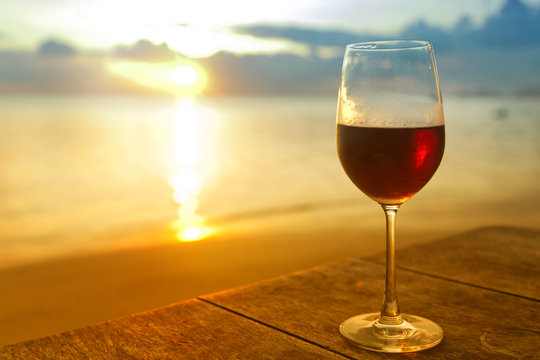 glass of red wine  on the beach at colorful sunset