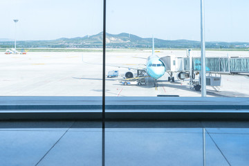 glass window and airplane in airport