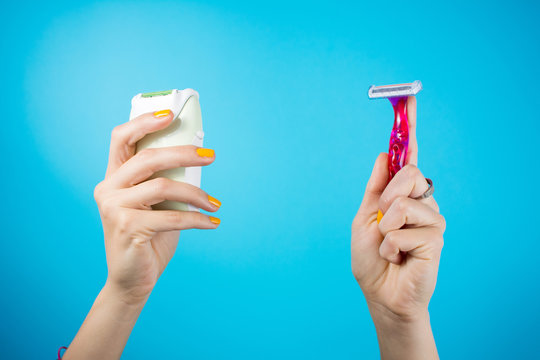Red shaver and epilator in woman hands