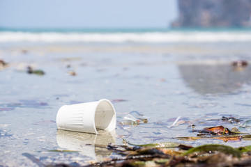 White plastic cup on the beach