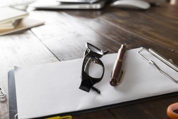 eyeglasses, pen and notepad on office desk