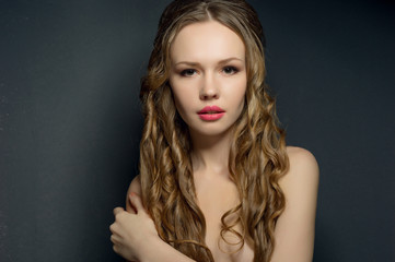 Portrait of a beautiful young woman on dark background.