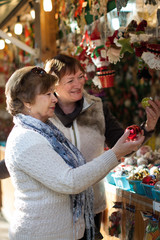 mature women choosing decorations at Christmas market