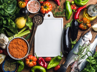 Ingredients for cooking healthy dinner. Raw uncooked seabass fish with vegetables, grains, herbs and spices over rustic wooden background, white ceramic board in center