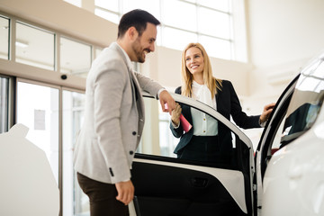 Salesperson showing vehicle to potential customer