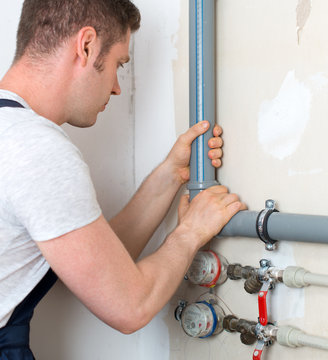 Male plumber assembling water pipes.