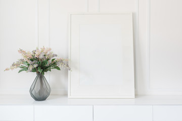 glass vase of flower with white picture frame