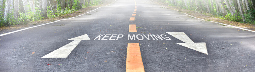 Words of keep moving with white arrow and yellow line marking on road surface in the national park