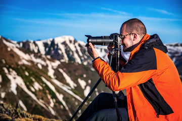 Young photographer with his camera and tripod in the mountains.