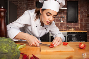 Female chef cook cutting vegetables in the kitchen  preparing a meal from tomatoes and broccoli