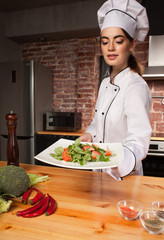 Female cook with fresh salad in her hands near chili pepper, broccoli, spices and pepper mill on the wooden table