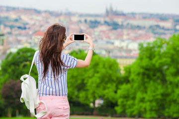 Young caucasian woman making photo of european old city by mobile phone from the observation place