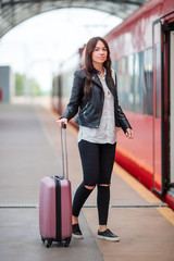 Young woman with luggage talking at train station. Caucasiam tourist waiting her express train while her vacation