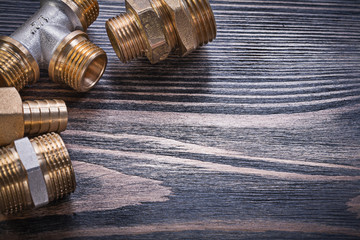 Composition of brass connectors on wooden background plumbing co