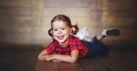 happy child girl laughing at empty wooden wall