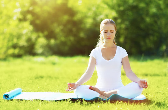 young woman enjoying meditation and yoga on green grass in summe