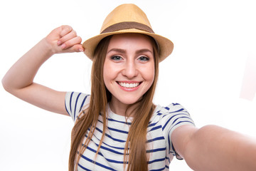 Happy cute woman making selfie over gray background.