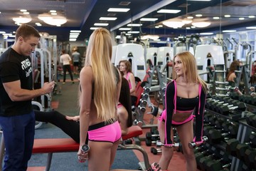 Blonde posing coach during training with dumbbells