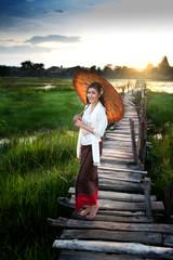 Woman standing on the bridge holding an umbrella