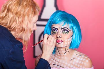 Professional make-up artist makes comic pop art make up. Creative beauty style.