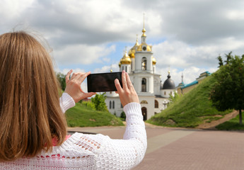 Girl taking pictures on mobile smart phone in front view Temple
