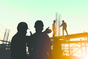 Silhouette engineer standing orders for construction crews to wo
